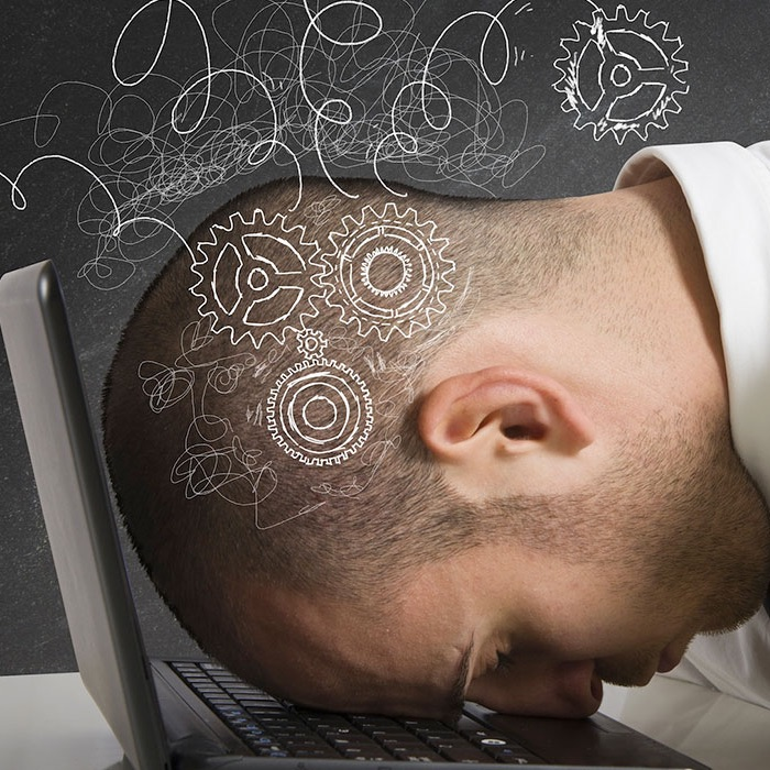Frustrated man resting head on the keyboard of his laptop