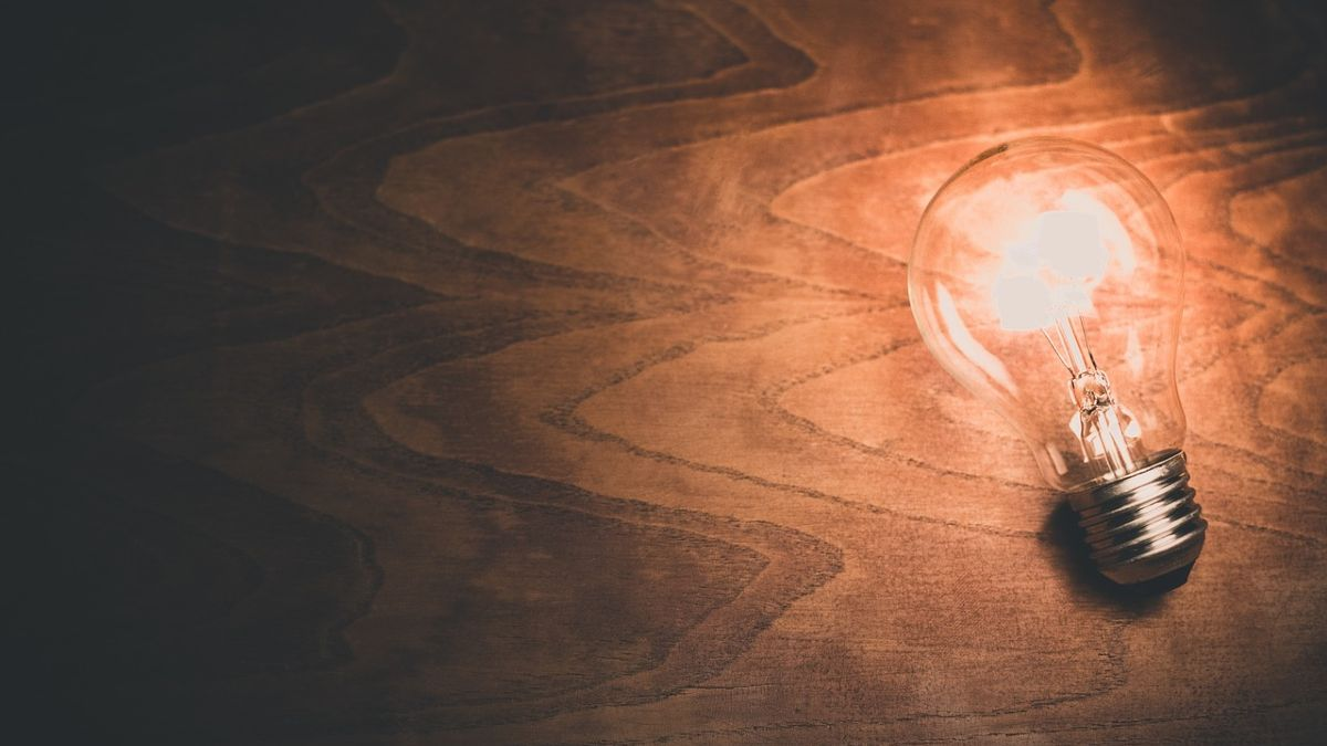 Photo of a lit lightbulb on top of a wooden table.