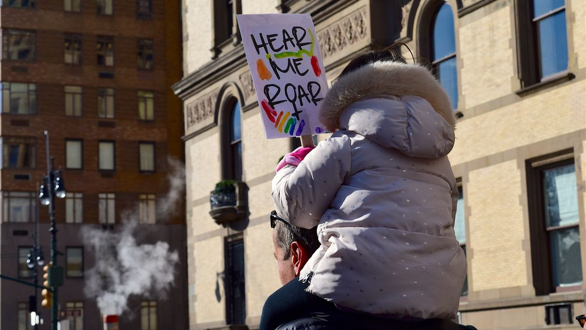 Child sitting on shoulders of her parent, holding a sign that reads HEAR ME ROAR
