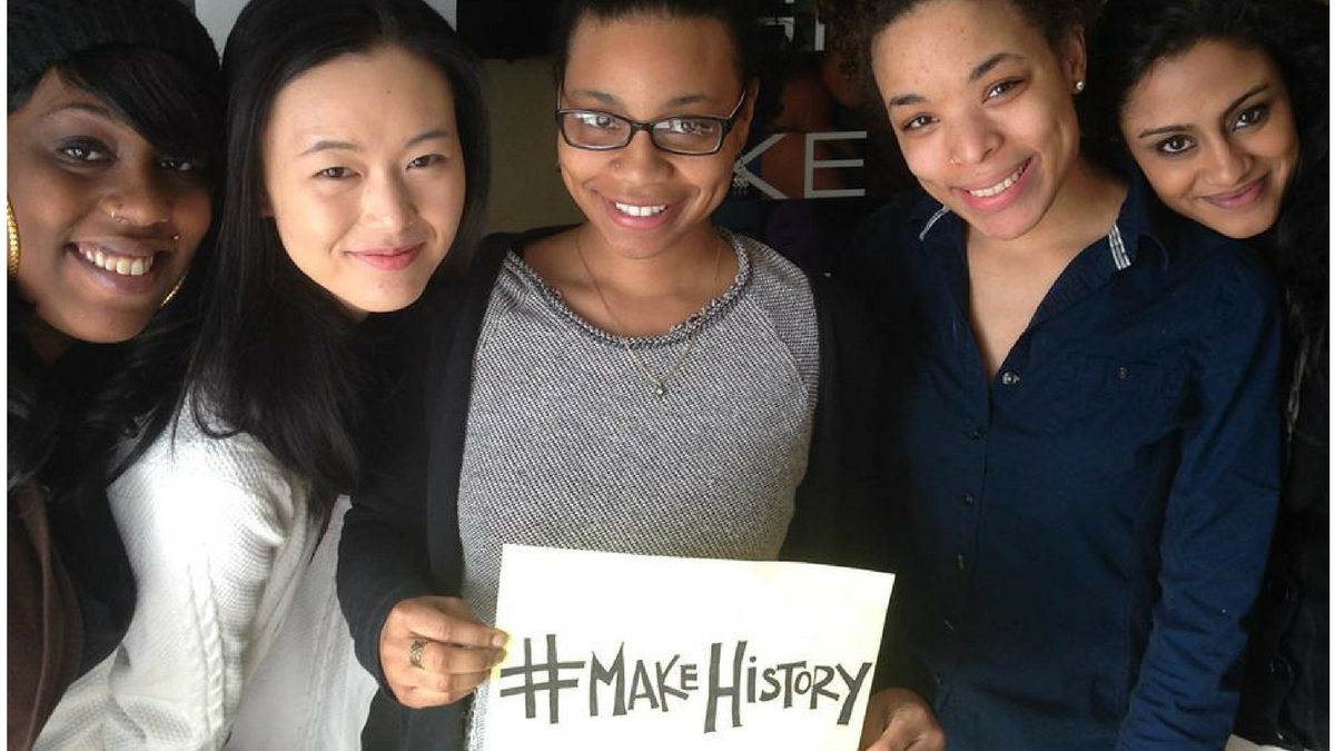 Photo of five girls holding up a sign that says make history.